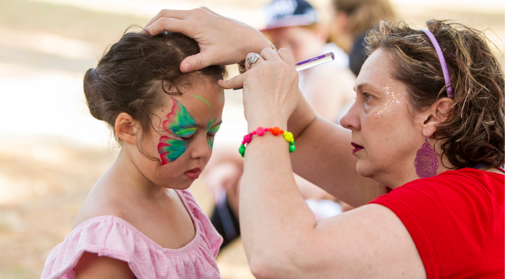 a face painter working on a girl's face