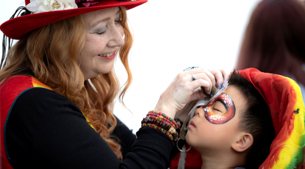 a face painter working on a boy's face