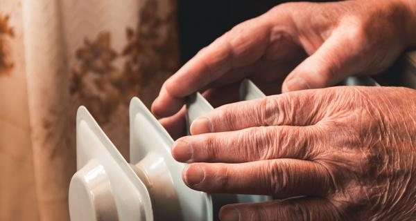 Older person warming hands over a heater