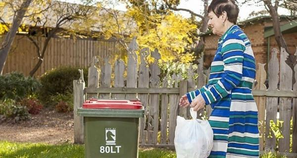 Image of lady putting out rubbish