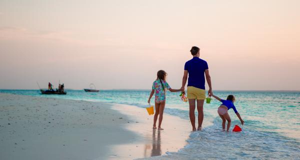 Father walking along beach holding hands with his children