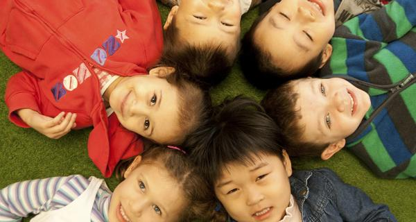 A group of multicultural children laying on the ground