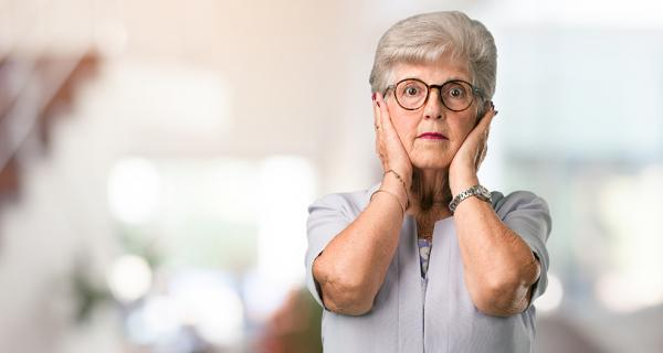 Older woman with hands over ears due to noise
