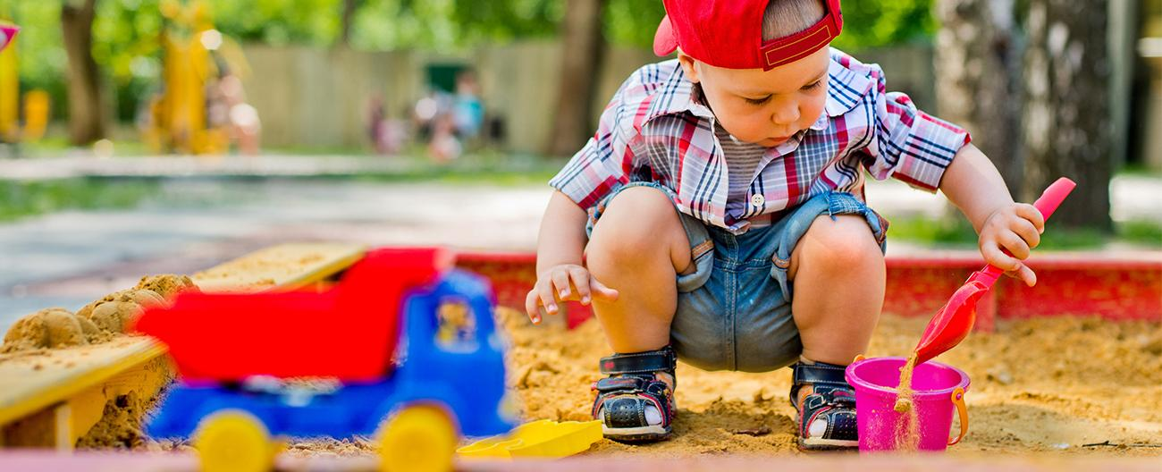 A little boy playing in a sandpit