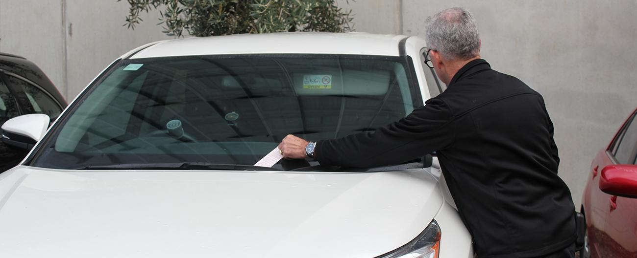 Parking fine being placed on car windscreen